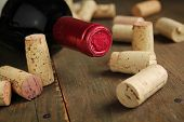 stock photo of liquor bottle  - Cork wine on a wooden table with a bottle of red wine - JPG
