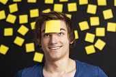 Happy student with a reminder on the head, and with more yellow paper notes in the background