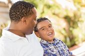 Happy African American Father and Mixed Race Son Talking in the Park.