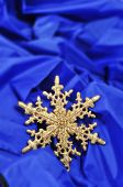 a golden christmas ornament in the shape of a snowflake on a blue fabric background