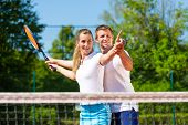 Man, tennis teacher, showing woman how to play the racket sport outdoors