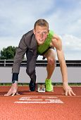 Conceptual image of an athlete (sprinter) ready to start a business career. Performance in business is top sport