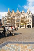 stock photo of clydesdale  - A pair of horses add charm to the famous medieval Guild Houses of Antwerp Belgium - JPG