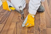Worker Nailed Old Wooden Floor Cracks