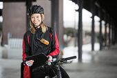 Portrait of young female cyclist in protective gear with courier bag using digital tablet