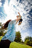 Pregnant mother in third trimester playing with her daughter in a park