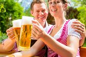 stock photo of stein  - Happy Couple sitting in Beer garden in summer and enjoying a glass of beer and the sun - JPG