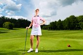 Young female golf player on course, she presumably does exercise