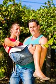 Winegrower man carries a woman on his arms at the  vineyard smiling