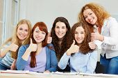 Happy successful women holding thumbs up in a university class