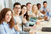Many happy students holding their thumbs up in class