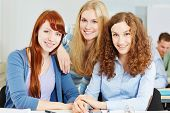 Three young happy attractive women in university class