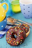 Colorful donuts on blue wooden table, selective focus
