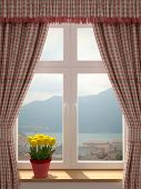 stock photo of window washing  - Just washed window with a wonderful view of the village and decorating in country style curtains