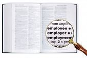 A magnifying glass held over a dictionary looking at the words Employee, Employer and Employment enl