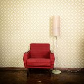 Vintage room with old fashioned armchair, standart lamp, old fashioned wallpaper and weathered woode