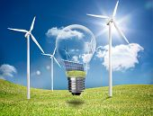 Light bulb showing solar panels and turbines hovering in a green field with wind turbines in the sunshine