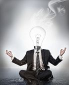 Businessman with bulb head sitting in meditation position with smoke rising on grey background