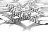 Group of forks with their tines intertwined with reflection on a shiny metal surface. Horizontal format