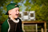 Portrait of child in catcher's gear laughing while playing baseball