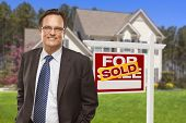 Male Real Estate Agent in Front of Sold Home For Sale Sign and House.