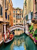stock photo of gondola  - Scenic canal with gondola and flowers - JPG