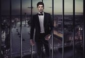 Elegant man over evening city background