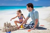 Happy father and his adorable little daughter at tropical beach making sandcastle