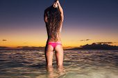 young sexy woman in bikini at the beach at sunset