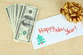 Dollar bills in envelope as gift at New year on wooden table close-up