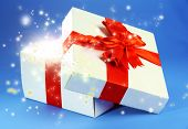 Gift box with bright light on it on blue background