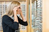 Side view of mid adult woman trying on eyeglasses in optician store