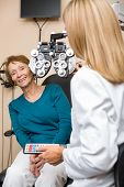 Smiling senior woman undergoing eye checkup while optometrist adjusting phoropter in store