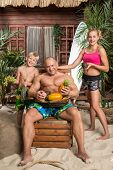 A family of three on a sandy beach with a basket of fruit, father sitting on chair