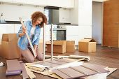 Woman Putting Together Self Assembly Furniture In New Home