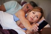 stock photo of early 50s  - Couple In Bed With Wife Suffering From Insomnia - JPG