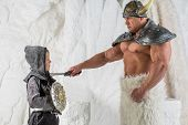 image of viking  - A muscular father in costume viking title young son by sword - JPG