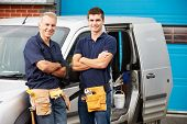 Workers In Family Business Standing Next To Van
