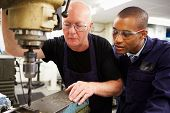 stock photo of overalls  - Engineer Teaching Apprentice To Use Milling Machine - JPG
