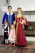 Father, mother, little daughter and son in medieval costumes stand near fireplace.