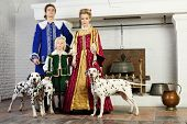 Father, mother and son in colorful medieval costume stand near fireplace with three dalmatians on le