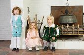 Two boys and girl in medieval costumes are near fireplace with boiler and logs.