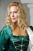 Portrait of pretty blonde woman in green medieval costume looking away.