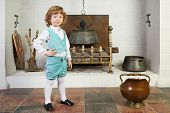 Little boy in medieval costume stands near fireplace with logs and boiler.