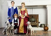 Father, mother and happy little son in medieval costume stand near fireplace with three dalmatians o