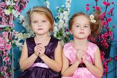 Two cute little girls in dresses sit with folded hands in prayer in room with flowers.