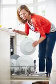 Woman Loading Plates Into Dishwasher