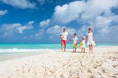 stock photo of family bonding  - Happy beautiful family on a Caribbean holiday vacation - JPG