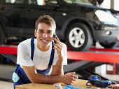 foto of auto repair shop  - portrait of mechanic talking on mobile phone in auto repair shop - JPG