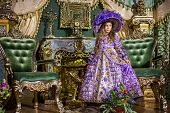 The girl in old-fashioned dress in beautiful room with gilded furniture